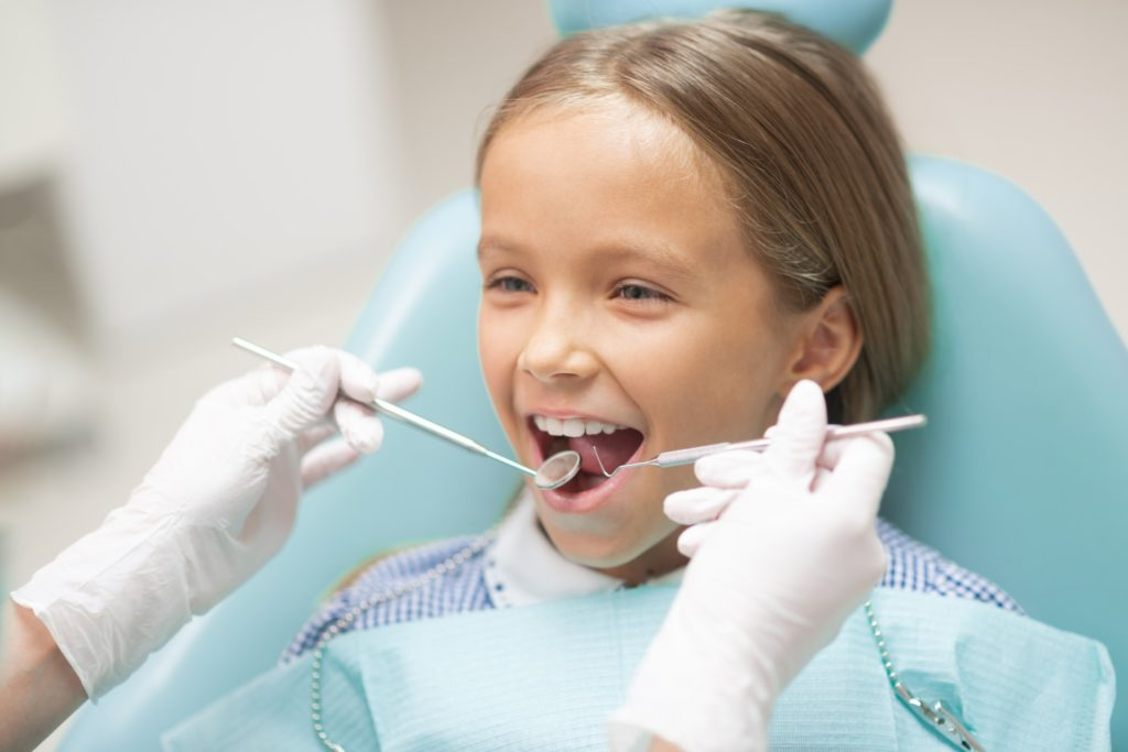 A young girl sitting in a dental chair getting a dental checkup