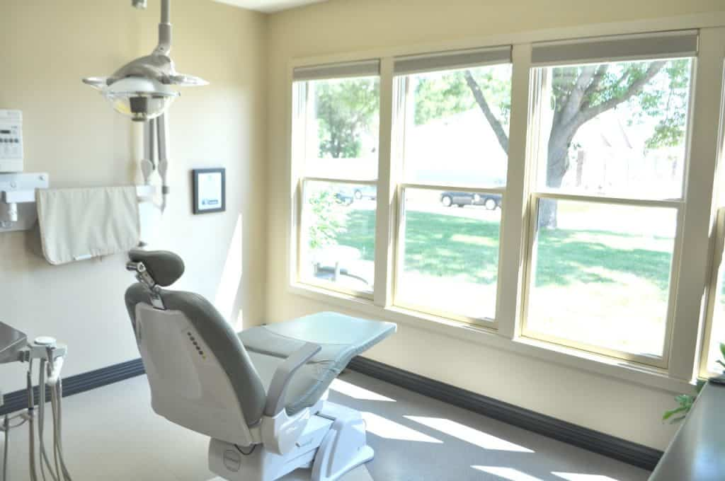 A dental exam room with a dental chair in the middle facing a row of windows